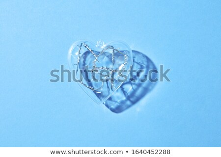 Transparent plastic heart with twisted wire inside. Stock photo © artjazz