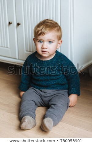 Children concept. Little small infant with appealing blue eyes, plump cheeks and blonde hair sits on Stock photo © vkstudio