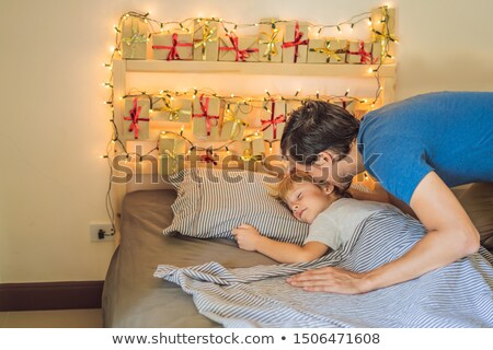 Dad wakes up little boy in the morning and home made advent calendar on a shelf. Winter seasonal tra Stock photo © galitskaya
