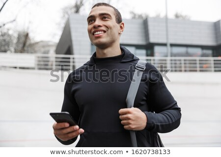 Handsome young smiling sportsman carrying sportsbag Stock photo © deandrobot
