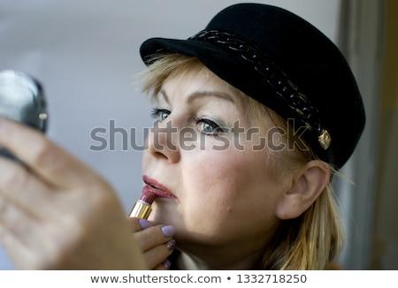 Elderly woman applying lipstick Stock photo © photography33