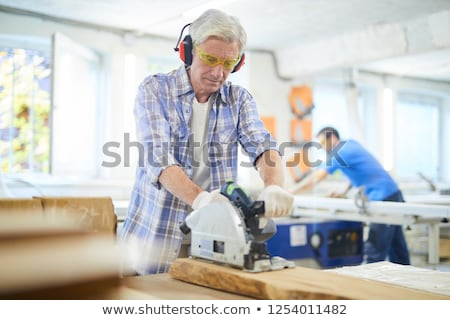 Grey-haired man with circular saw Stock photo © photography33