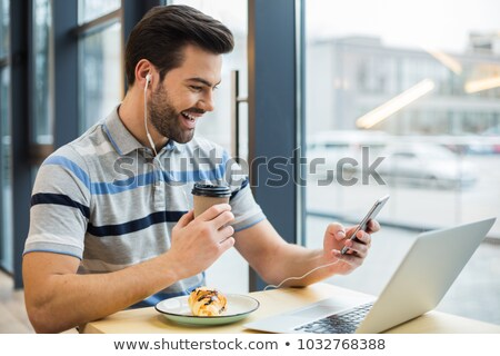 Handsome man looking at his laptop while having lunch in the kitchen  stock photo © wavebreak_media