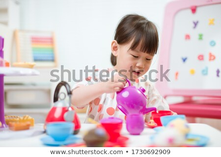 Young girl playing with a tea set Stock photo © photography33