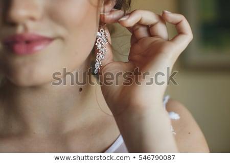 Donna indossare lucido diamante orecchini Foto d'archivio © dolgachov