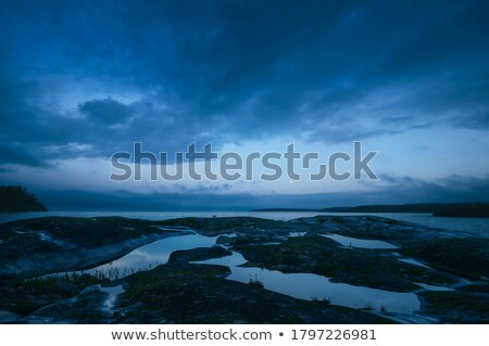 Water puddle on a rocky shore during sunset Stock photo © Mps197