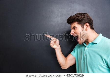 portrait of angry man pointing finger away stock photo © deandrobot