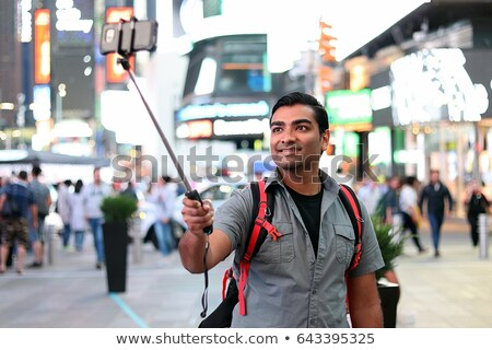 Smiling young backpacker using a selfie stick Stock photo © dash