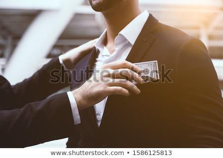 Business man putting money bribe in pocket. Stock photo © RAStudio
