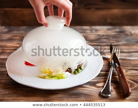 Female hand lifts to up cloche  from a plate with hot food at re Stock photo © Yatsenko