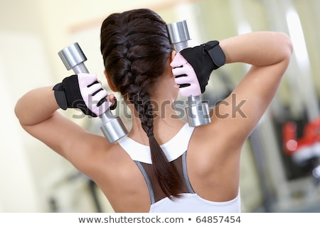 back of young fit woman holding dumbbells on white stock photo © julenochek