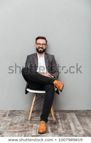 Caucasian young bearded man sitting isolated over grey wall Stock photo © deandrobot