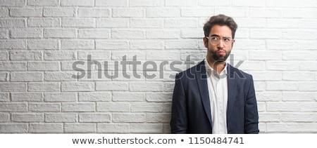 Portrait of a puzzled businessman in eyeglasses Stock photo © deandrobot