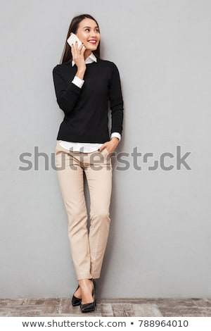 Woman in sweater with arm in pocket talking by smartphone Stock photo © deandrobot
