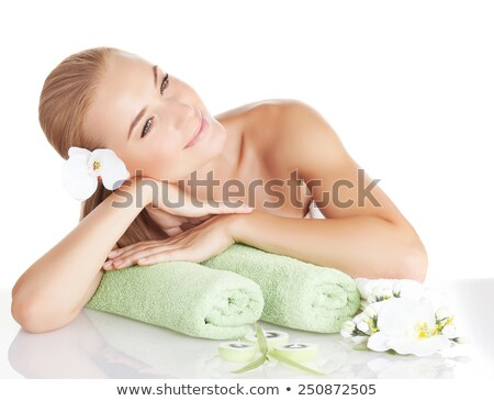 Young woman on massage table with orchid flower in hair Stock photo © IS2