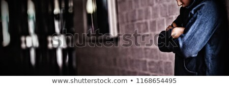 Boy standing alone by wall in corridor at school Stock photo © wavebreak_media