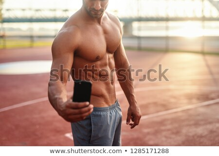 Handsome young sportsman taking selfie with mobile phone Stock photo © deandrobot