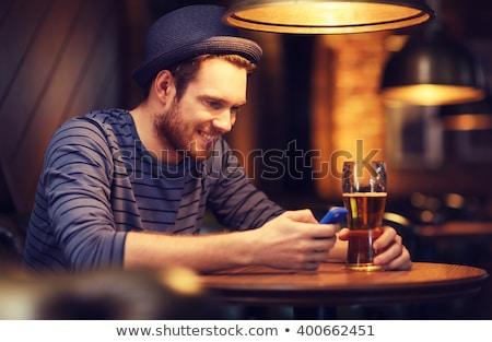 Man smartphone drinken bier bar pub Stockfoto © dolgachov