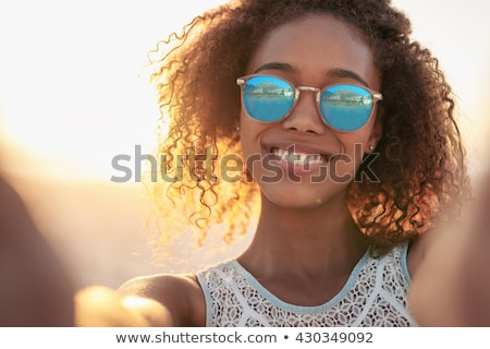 Image of beautiful woman 20s wearing sunglasses looking for some Stock photo © deandrobot