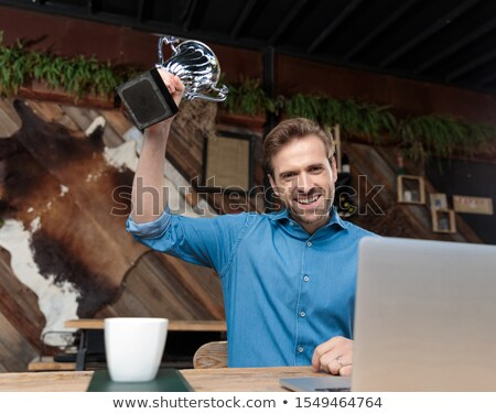 seated casual man holding his trophy in the air stock photo © feedough