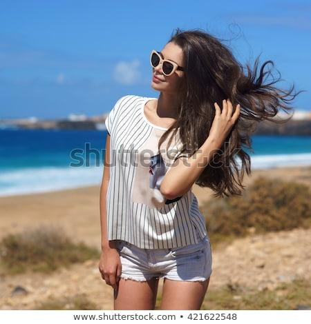 Opalony dziewczyna długie włosy elegancki szorty plaży Zdjęcia stock © ElenaBatkova