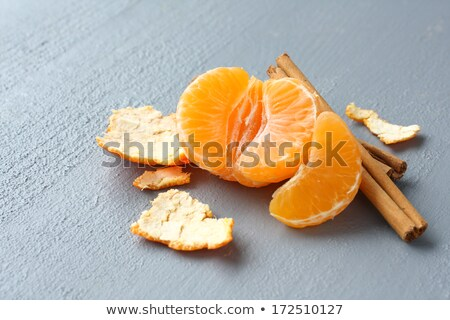 Open fresh mandarin with cinnamon sticks on gray background Stock photo © Melnyk