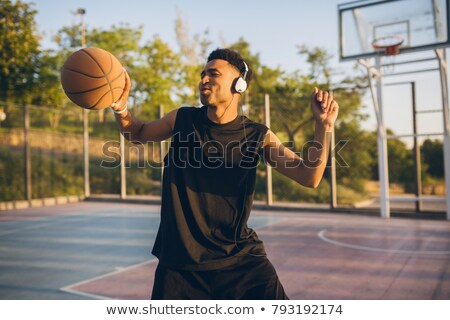 young active man with ball listening to music in headphones stock photo © pressmaster