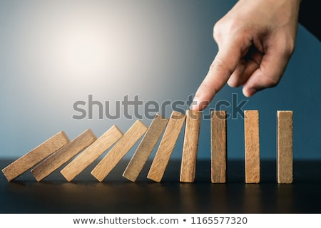 Close up of businessman hand Stopping Falling wooden Dominoes ef stock photo © Freedomz