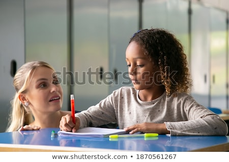 Side view young female teacher teaching schoolkid at desk in classroom of elementary school Stock photo © wavebreak_media