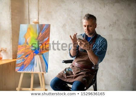 Casual painter with smartphone sitting in studio and scrolling in mobile phone Stock photo © pressmaster