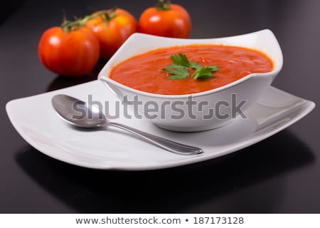 Black restaurant plate of creamy tomato soup on black table background with stone chopping board and Stock photo © DenisMArt