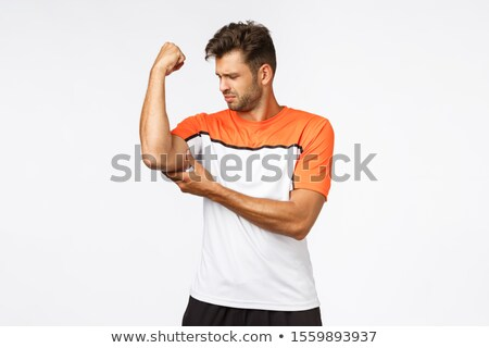 Upset gloomy handsome young man feeling weak as raising arm, touching his muscle and frowning sad, g Stock photo © benzoix
