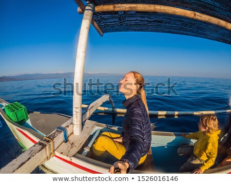 Mother and son travelers meets dawn in the sea on a boat Stock photo © galitskaya