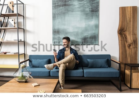 Stock photo: Happy young man sitting on sofa at home
