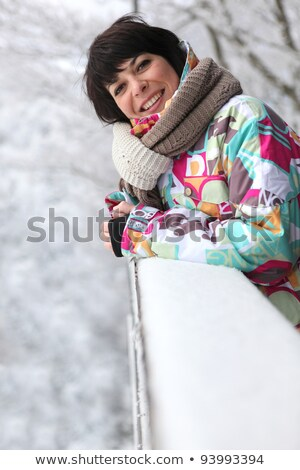 Woman leaning against a snow-covered ledge Stock photo © photography33