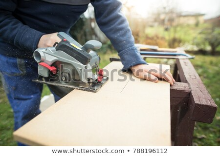 Carpenter sawing a piece of wood Stock photo © photography33