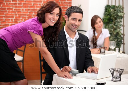 Woman leaning over a man in a restaurant with other diners in the background Stock photo © photography33