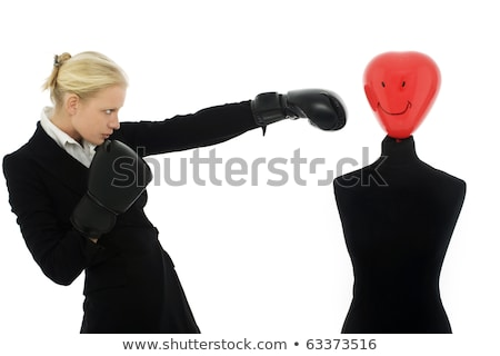 businesswoman with aggressive air wearing boxing gloves and punches a dummy stock photo © ambro