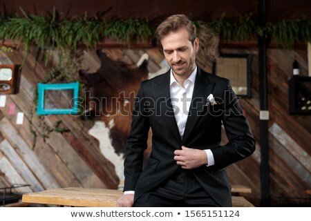 Stock photo: business man looking down while fixing his jacket