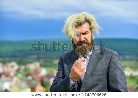 blond hipster business man smoking a cigarette stock photo © feedough