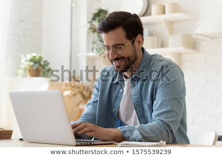 happy male student sitting at the table with laptop stock photo © deandrobot