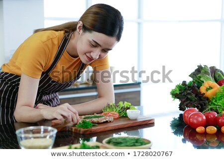 Concentrated pretty young woman cooking on kitchen at home Stock photo © deandrobot