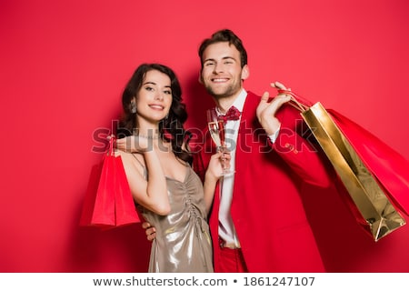 Young attractive man wearing suit and holding shopping bags Stock photo © zurijeta