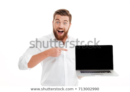 smiling young man standing and holding blank screen laptop stock photo © deandrobot