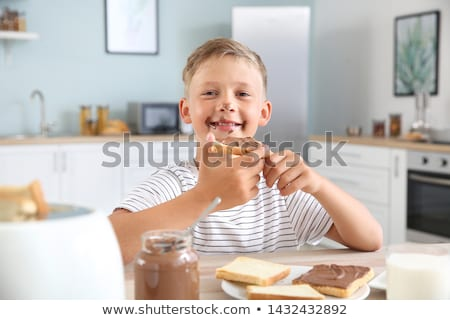 portrait of little boy eating chocolate stock photo © phbcz