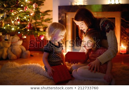 young mother and her two children opening a christmas presents b stock photo © dashapetrenko