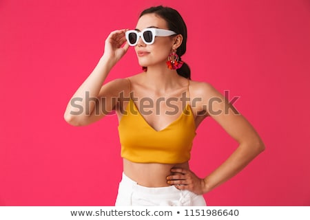 beautiful woman wearing glasses posing over pink background stock photo © deandrobot