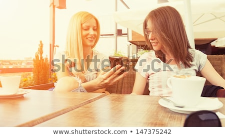 two cheerful women using cell phones and laughing in cafe stock photo © deandrobot