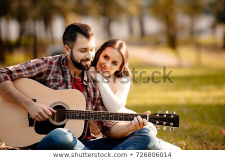woman leaning on man's shoulder while he plays guitar Stock photo © feedough