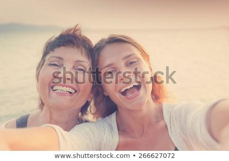 moeder · dochter · strand · glimlach · camera · horizontaal - stockfoto © iofoto